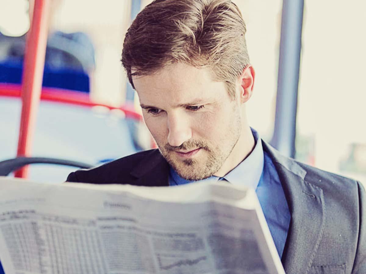Mann liest Zeitung im Bus.