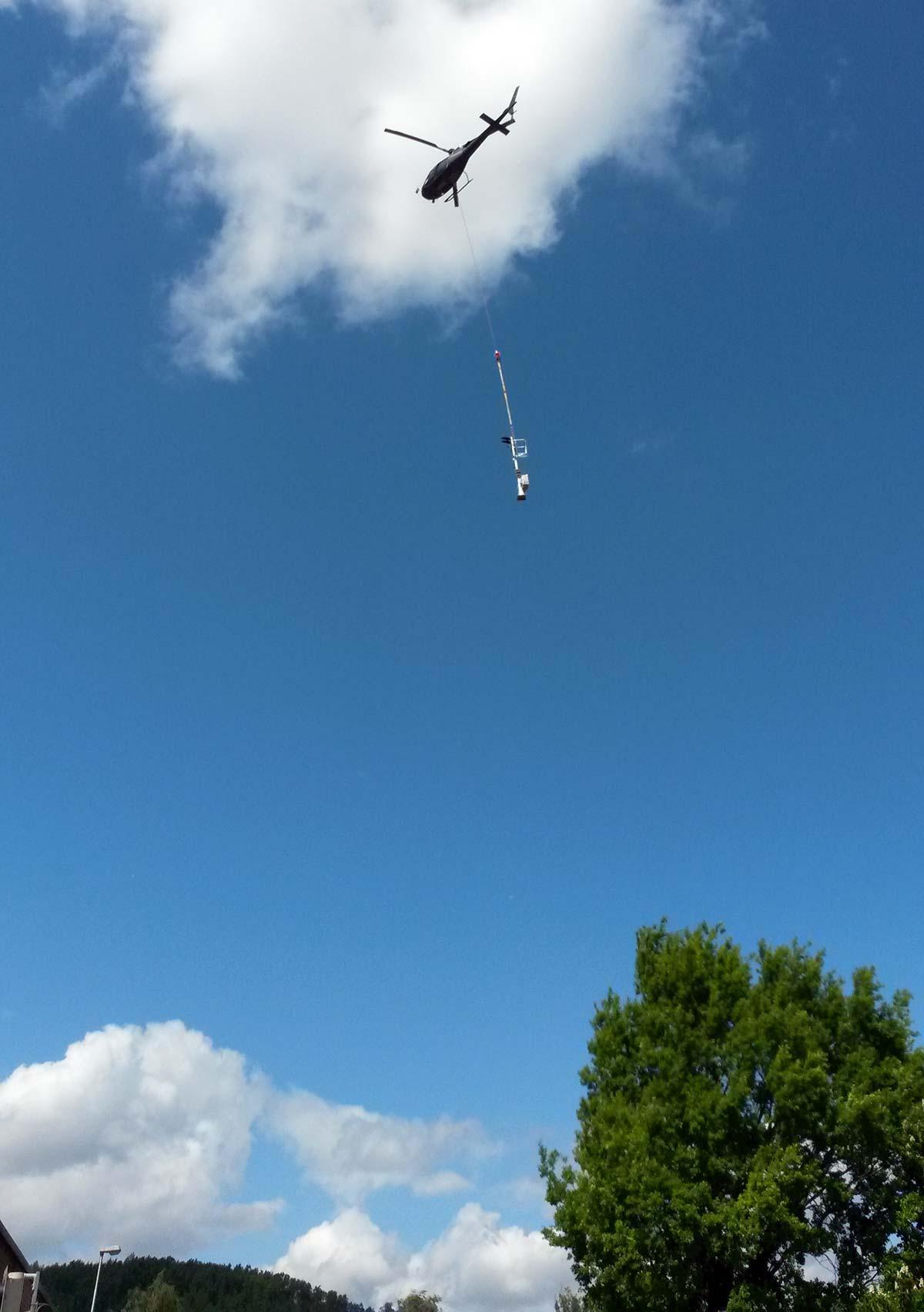 Ein Signalmast hängt am Stahlseil am Hubschrauber.